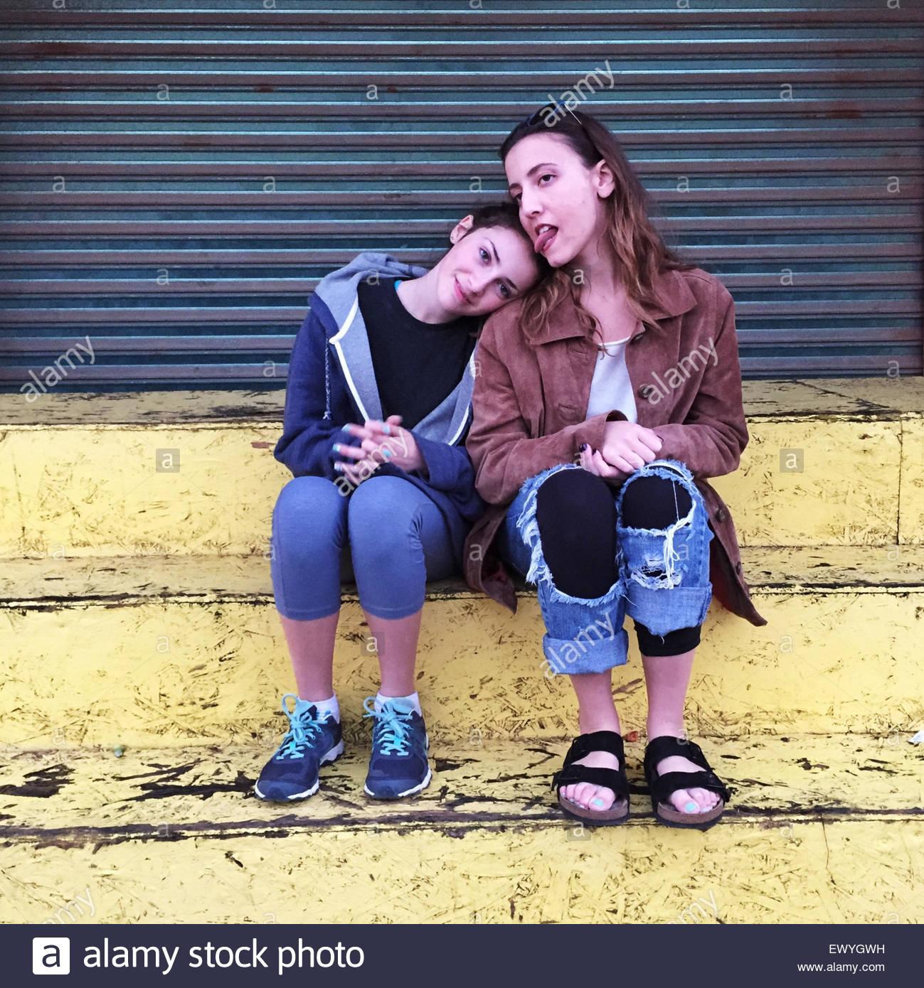 Zwei Mädchen sitzen auf einem Schritt über messing Stockbild