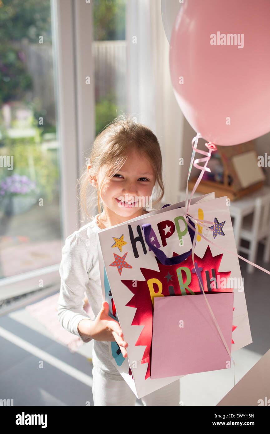 Mädchen halten Geburtstagsgeschenk und ein Ballon Stockbild
