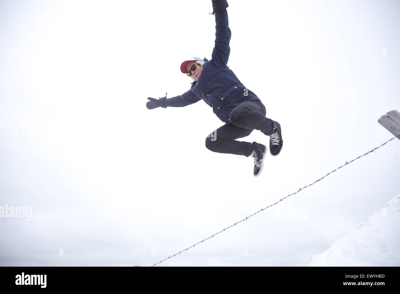 Niedrigen Winkel Blick eines jungen Mannes, der über den Zaun springen Stockbild