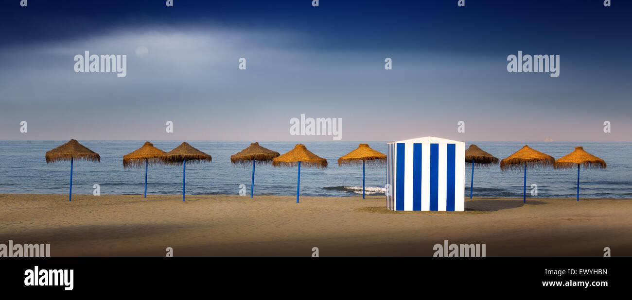 Hütte und Strand Sonnenschirme in einer Zeile, Valencia, Spanien Stockbild