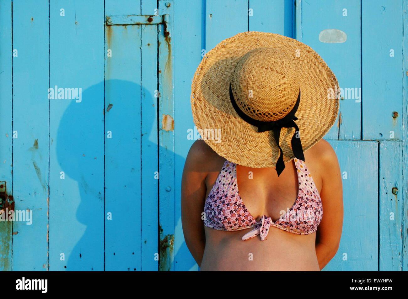 Schwangere Frau trägt einen Strohhut Stockbild