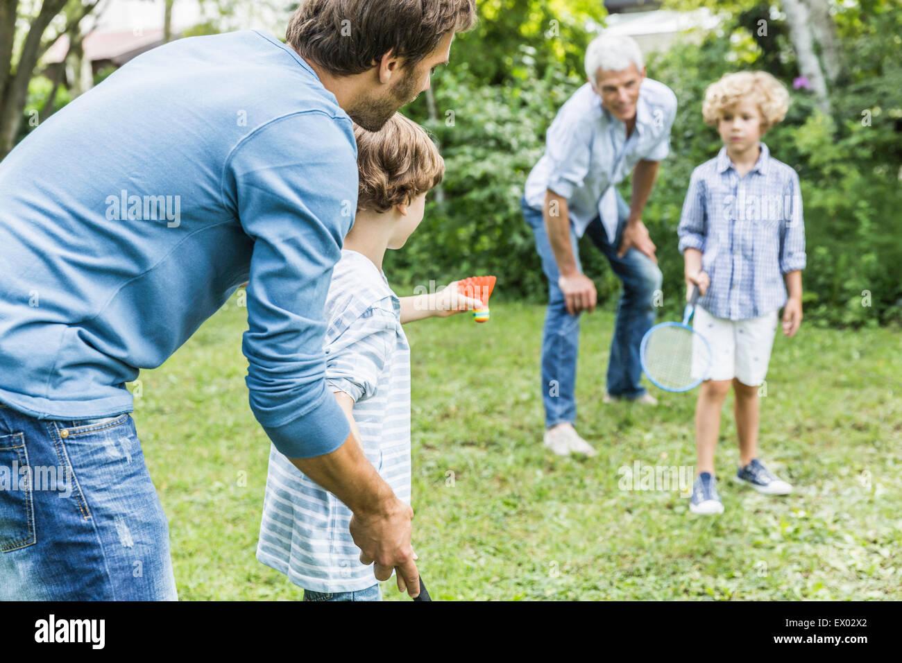 Reifer Mann und Sohn lehren Enkel Federball im Garten Stockbild