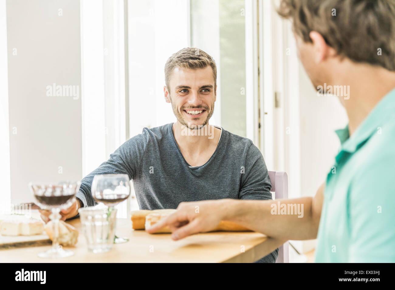 Zwei junge Männer im Chat am Tisch auf Party im Speisesaal Stockbild