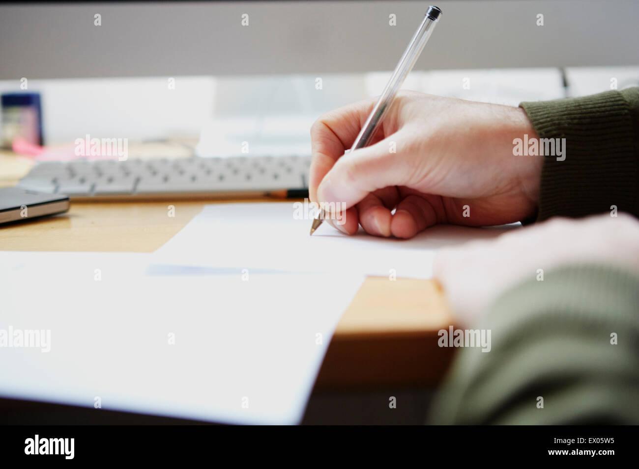 Mann mit Stift auf Papier schreiben Stockbild