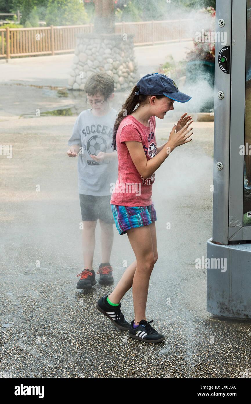 Kinder erfrischen Sie sich mit Hilfe einer erfrischenden Nebel Maschine in einem Park. Stockbild