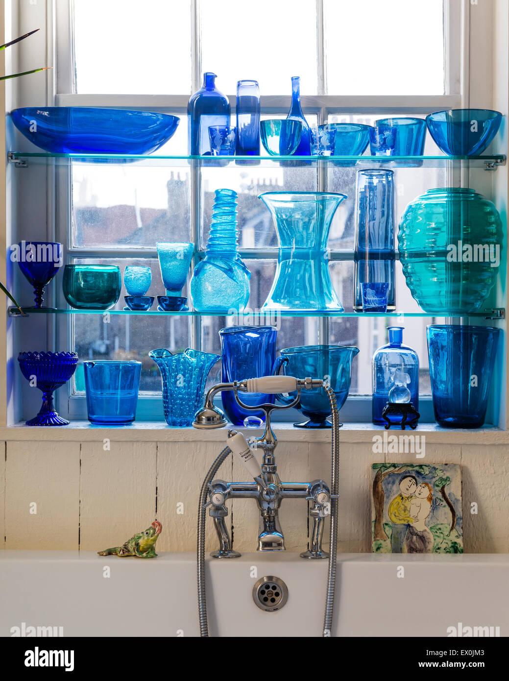 Sammlung von blauen Glaswaren auf Regal im Badezimmer Stockbild