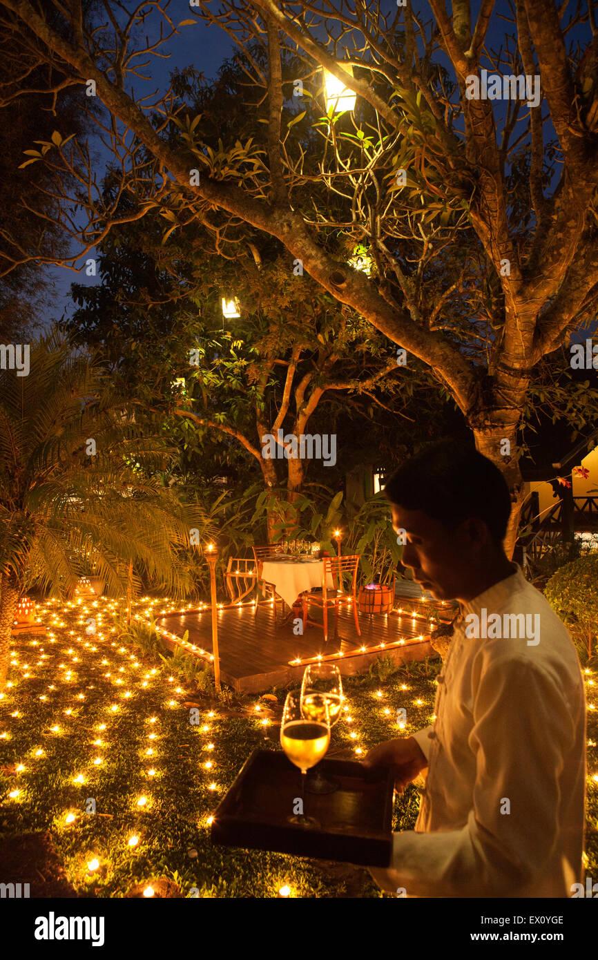 Eine spezielle 500 Candle Dinner mit Kellner in der Abenddämmerung. Hotel La Residence Phou Vao. Luang Prabang, Stockbild