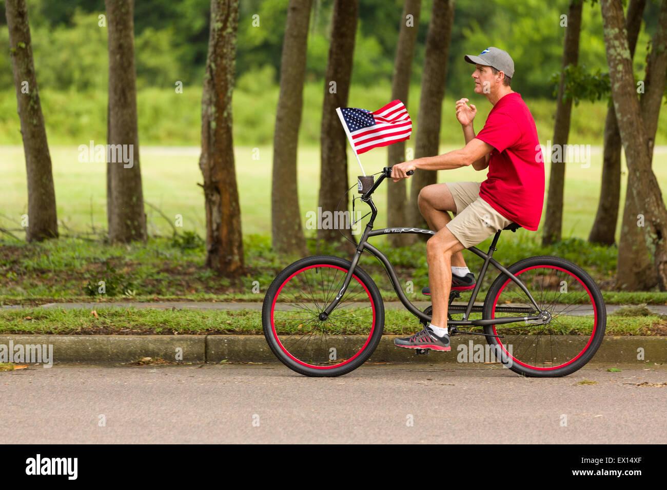 Ein Radfahrer fährt vorbei mit amerikanischen Flagge während der Daniel Insel NABHÄNGIGKEIT Tagesparade Stockbild