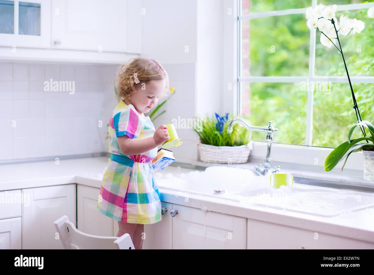 Kind abwaschen. Kinder waschen Teller und Tassen. Kleines Mädchen ...
