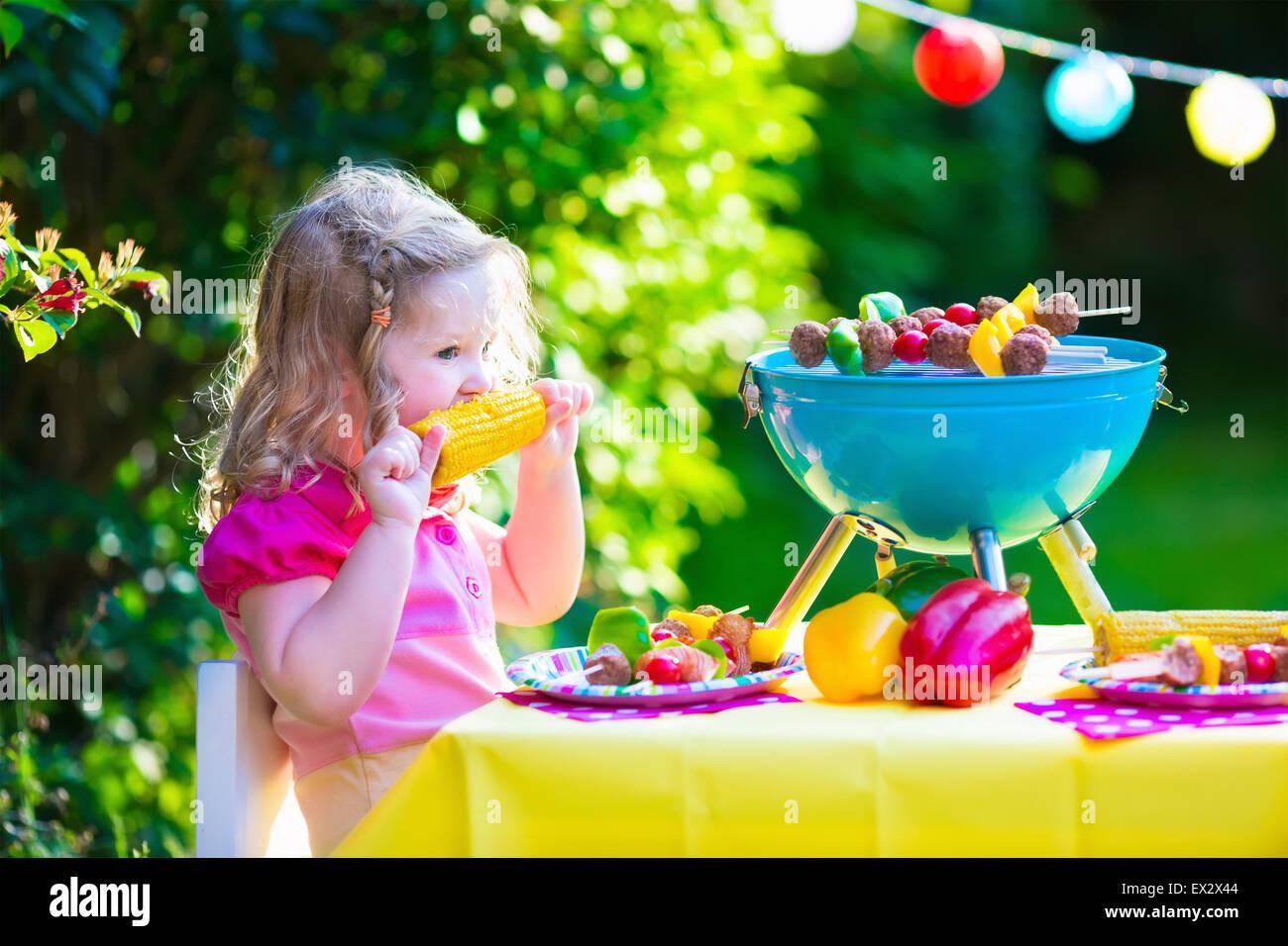 Kinder Grillen von Fleisch. Familien-Campingplatz und Grill genießen. Kleines Mädchen am Grill vorbereiten, Stockbild