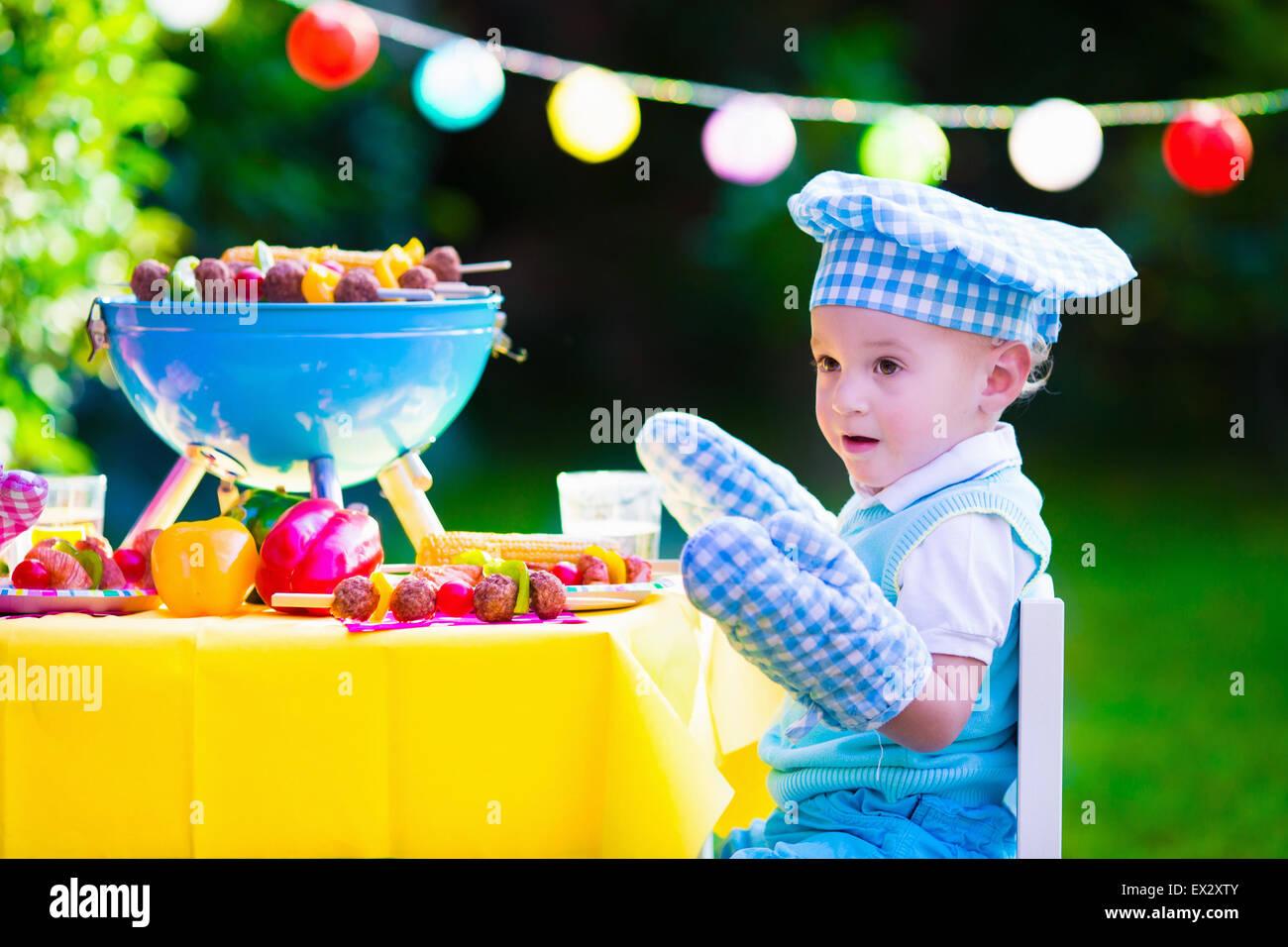Kinder Grillen von Fleisch. Familien-Campingplatz und Grill genießen. Kleiner Junge am Grill vorbereiten, Steaks, Stockbild
