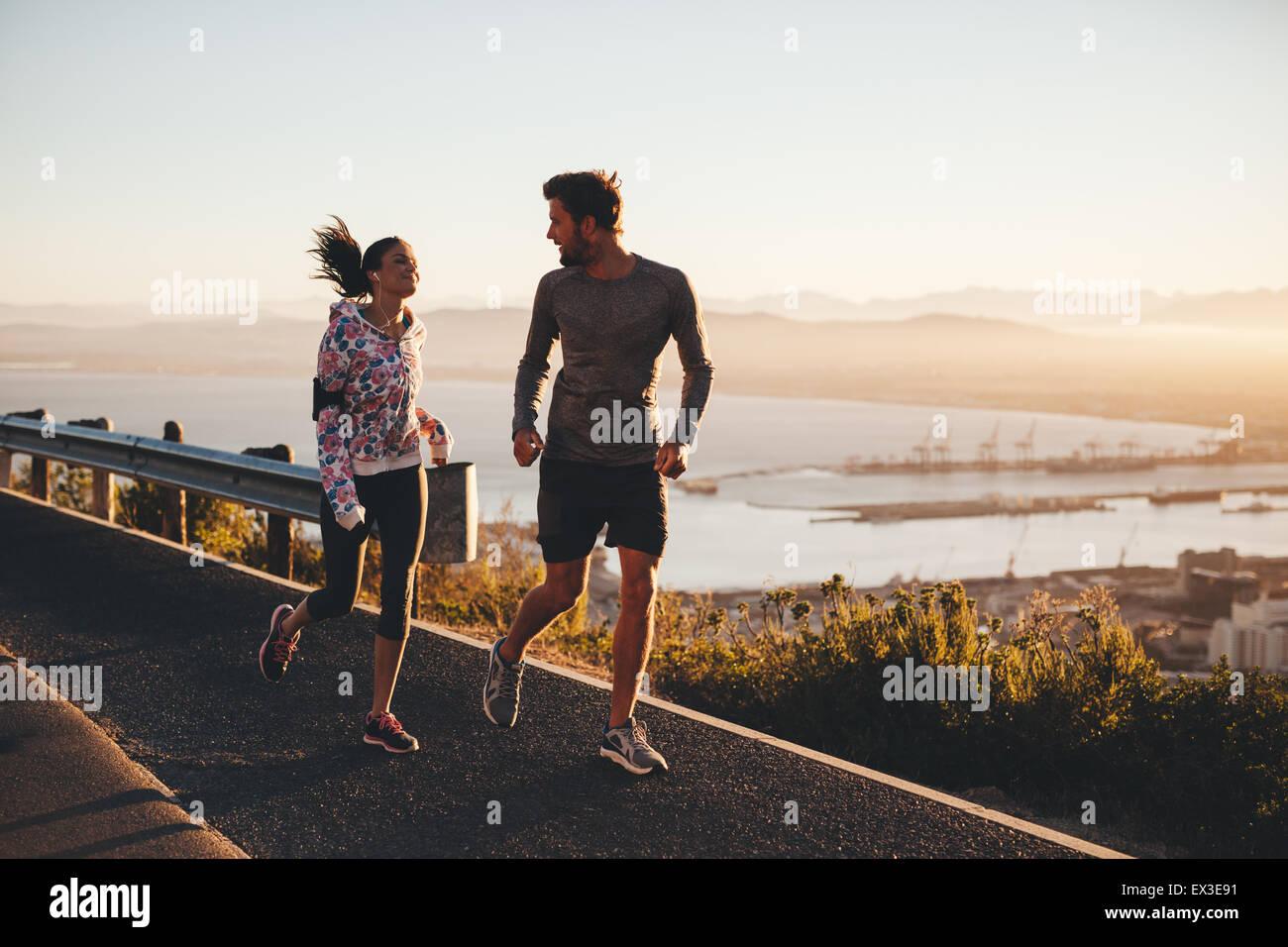 Aufnahme von zwei Menschen, die laufen auf einer Landstraße in Morgen. Junger Mann und Frau Joggen im Freien Stockbild