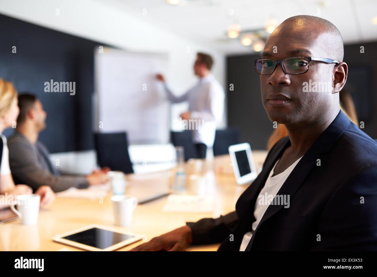 Schwarzen männlichen executive gerichtete Kamera mit einem ernsten Ausdruck während der Sitzung Stockbild