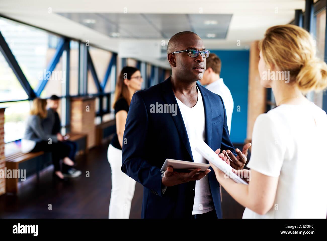 Schwarzen männlichen executive stehen und im Gespräch mit weißen Kollegin hält Notizblöcke Stockbild