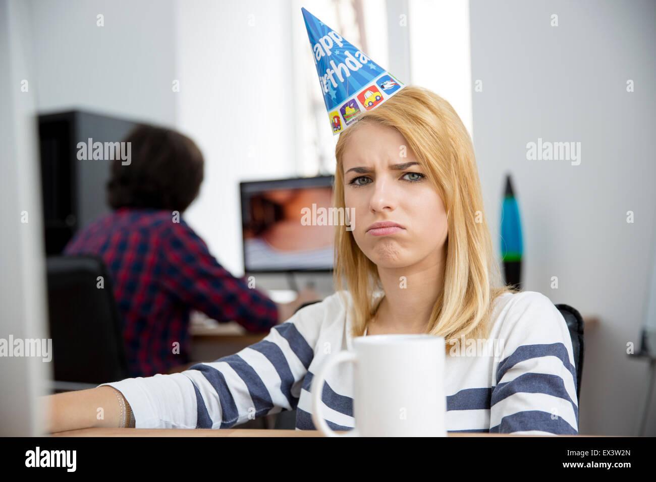 Traurige Frau mit Geburtstag Hut am Tisch im Büro sitzen und Blick in die Kamera Stockbild