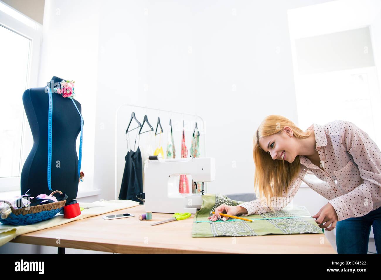 Lächelnde süße weibliche Schneider in Werkstatt Stockbild