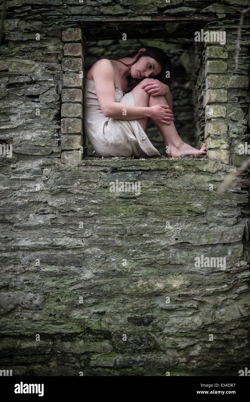 Eine junge dunkelhaarige Frau kaukasische Mädchen sitzen umarmen sich in einem verlassenen alten Haus Fenster Stockbild