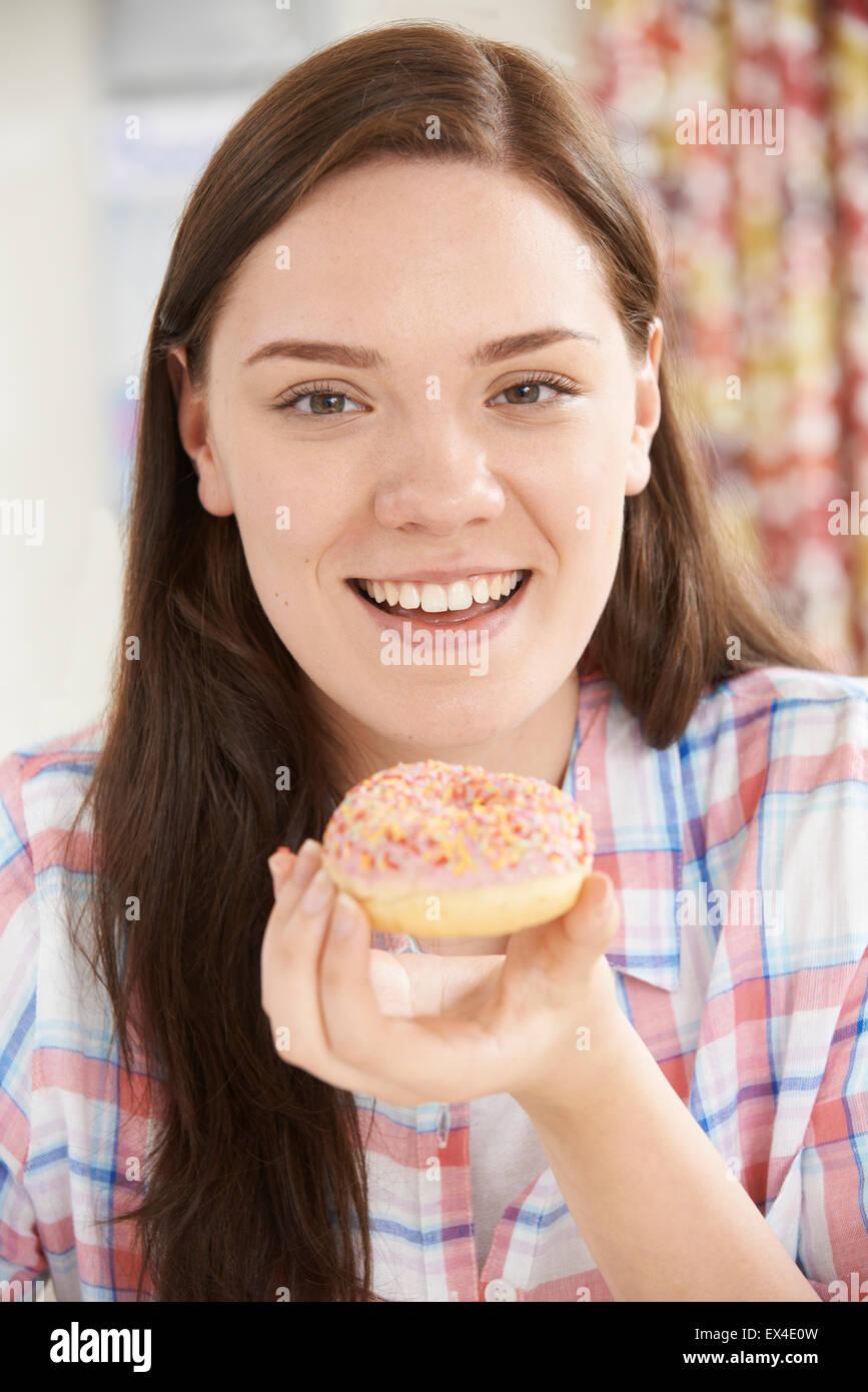 Portrait Of Smiling Teenager-Mädchen auf den Verzehr von Donut Stockfoto