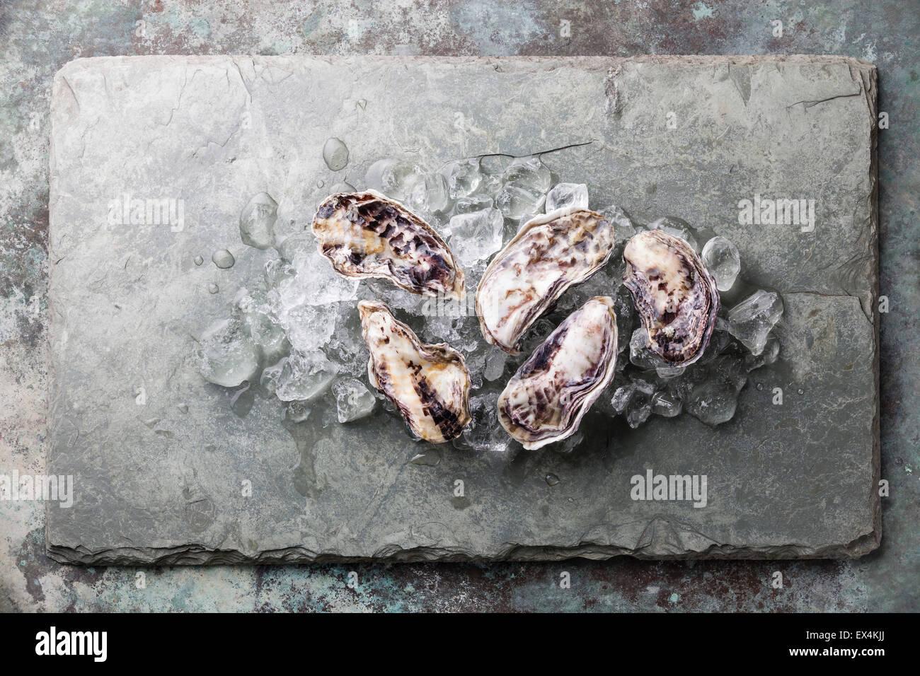 Fünf frische rohe Austern auf Stein Hintergrund mit Eis Stockbild