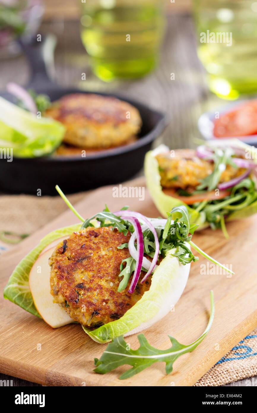 Vegane Burger mit Quinoa und Gemüse serviert mit Rucola und Salat Stockbild
