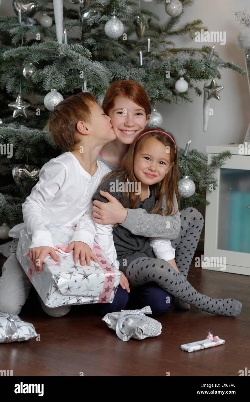 Heiligabend, glücklich Geschwister mit Weihnachtsgeschenke unter dem ...