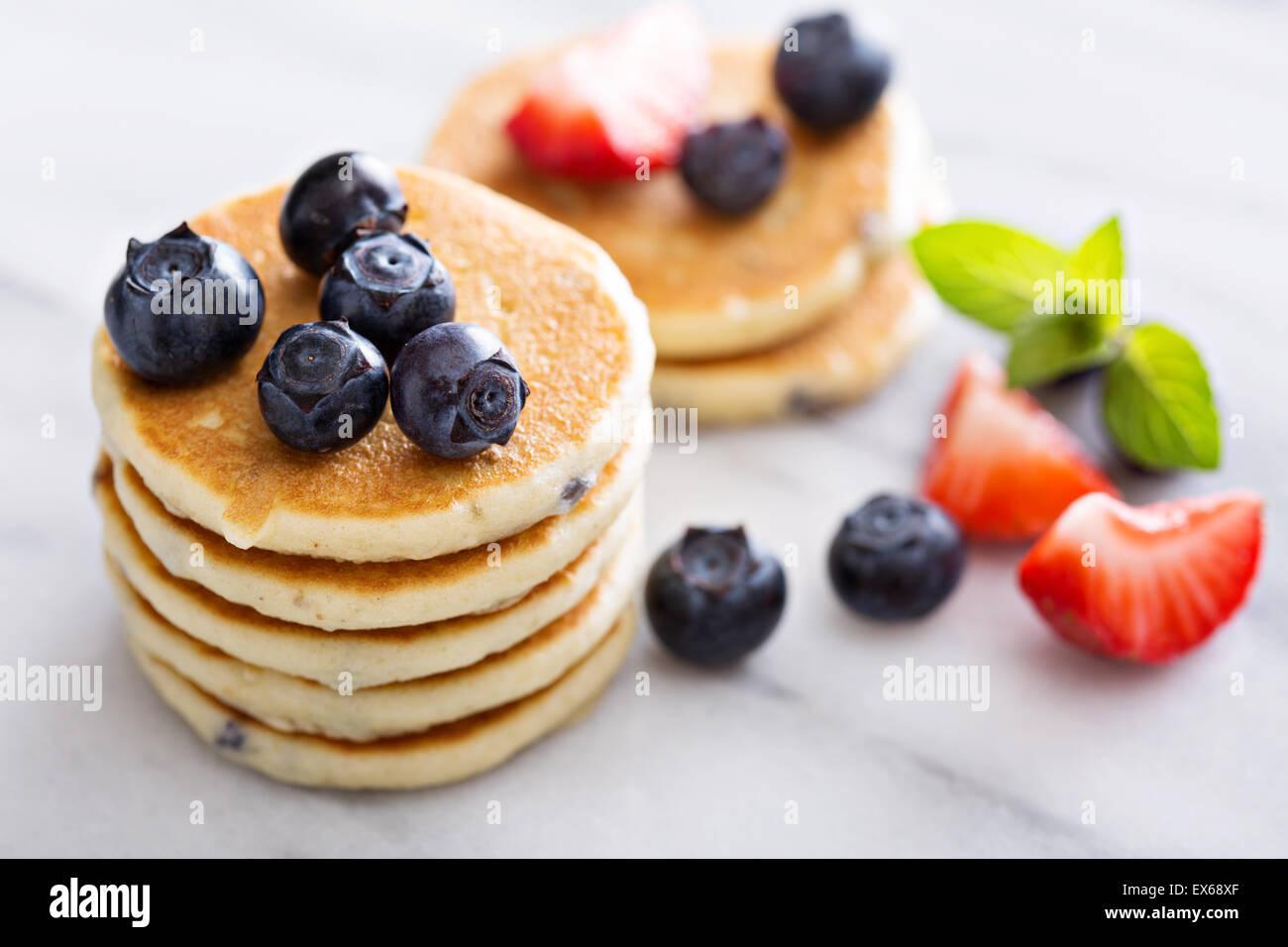 Stapel von kleinen Pfannkuchen mit Beeren auf Marmor Stockbild