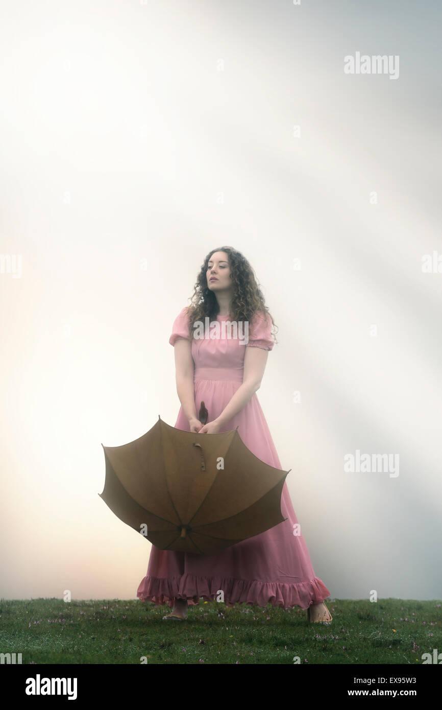 eine Frau in einem rosa Kleid mit einem Regenschirm Stockbild