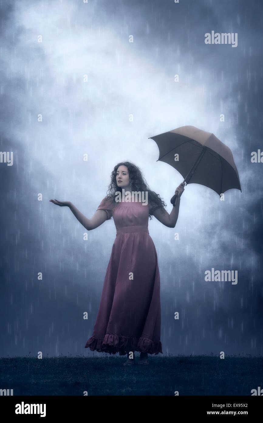 eine Frau in einem rosa Kleid mit einem Regenschirm im Regen Stockbild