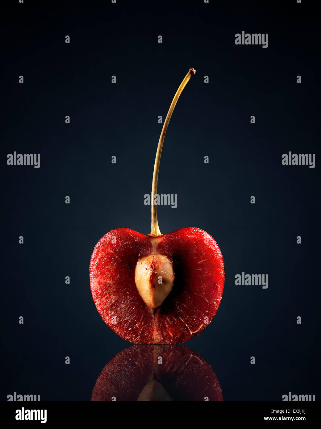 Red Cherry (halbiert) mit Reflektion auf dunklem Hintergrund Stockfoto