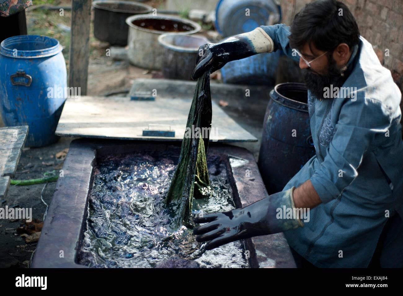 Muslimische Farbstoff master Untertauchens Block gedruckt Baumwollstoff in heißen indigo Lösung zum Färben, Bhuj Stockfoto