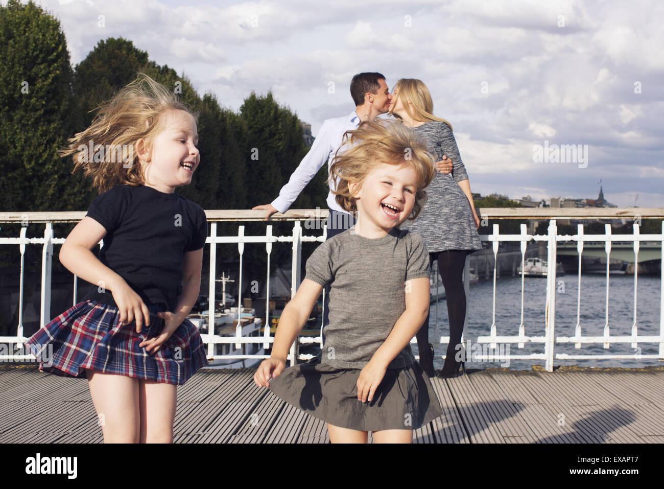 Mädchen im Freien spielen, während ihre Eltern im Hintergrund küssen Stockfoto