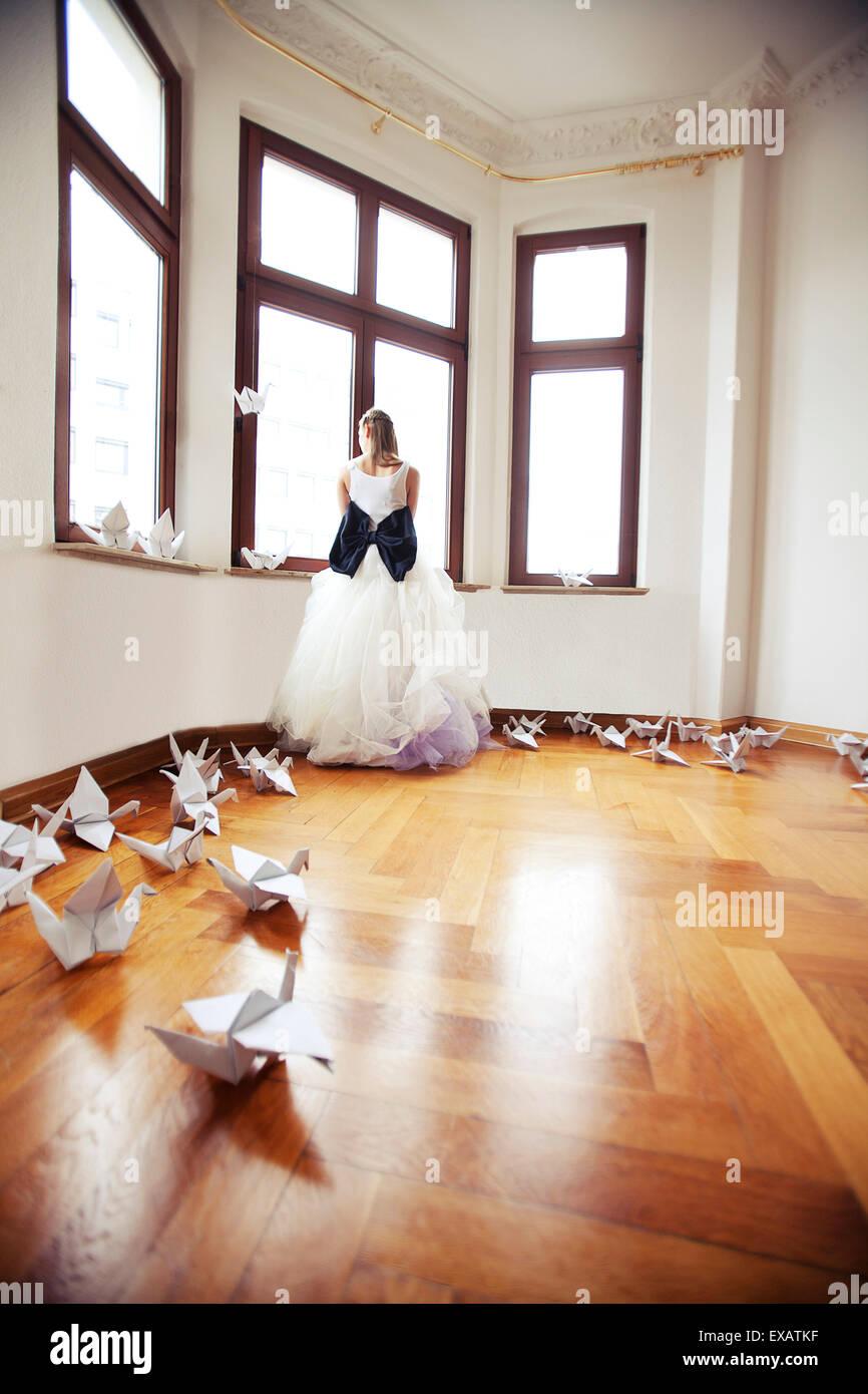 Braut in einer leeren Wohnung in einem alten Gebäude steht, schaut aus dem Fenster Stockbild
