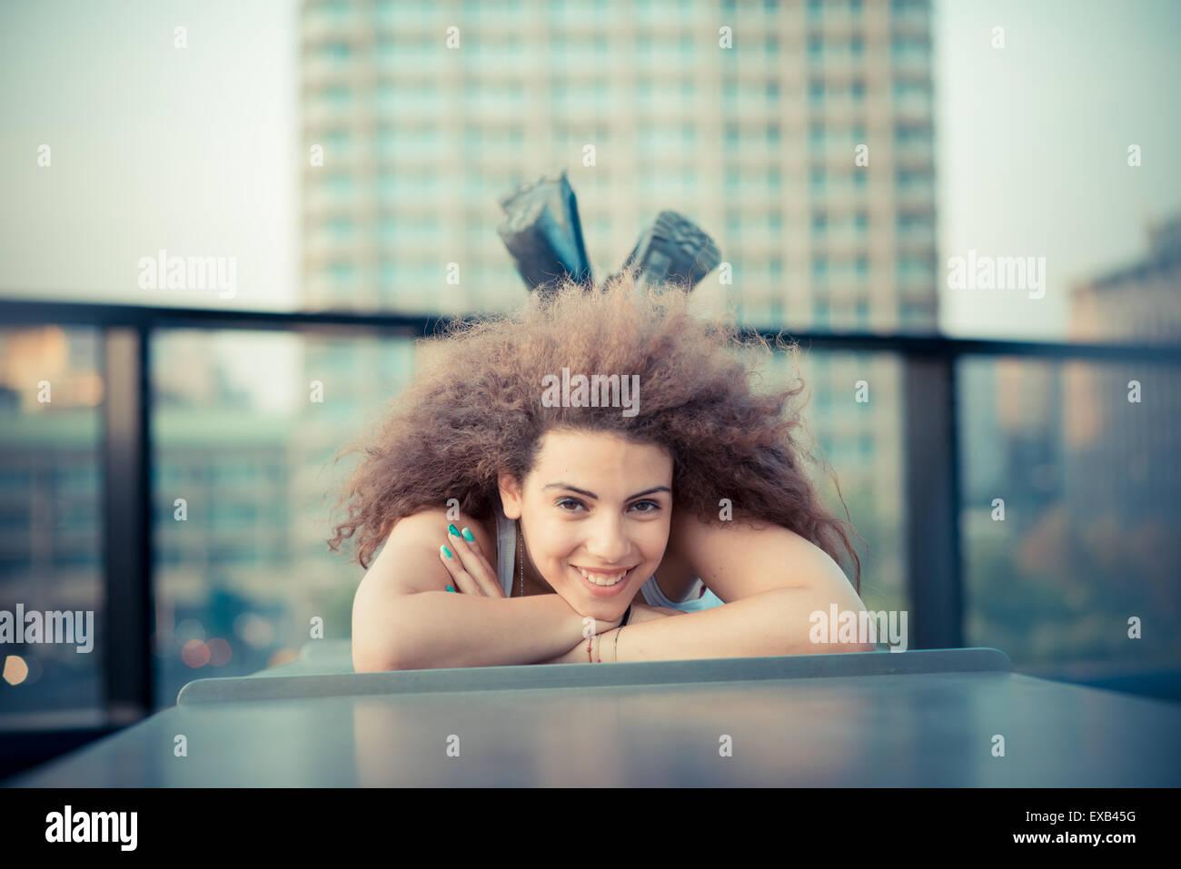 junge schöne langes lockiges Haar-Hipster-Frau in der Stadt Stockbild