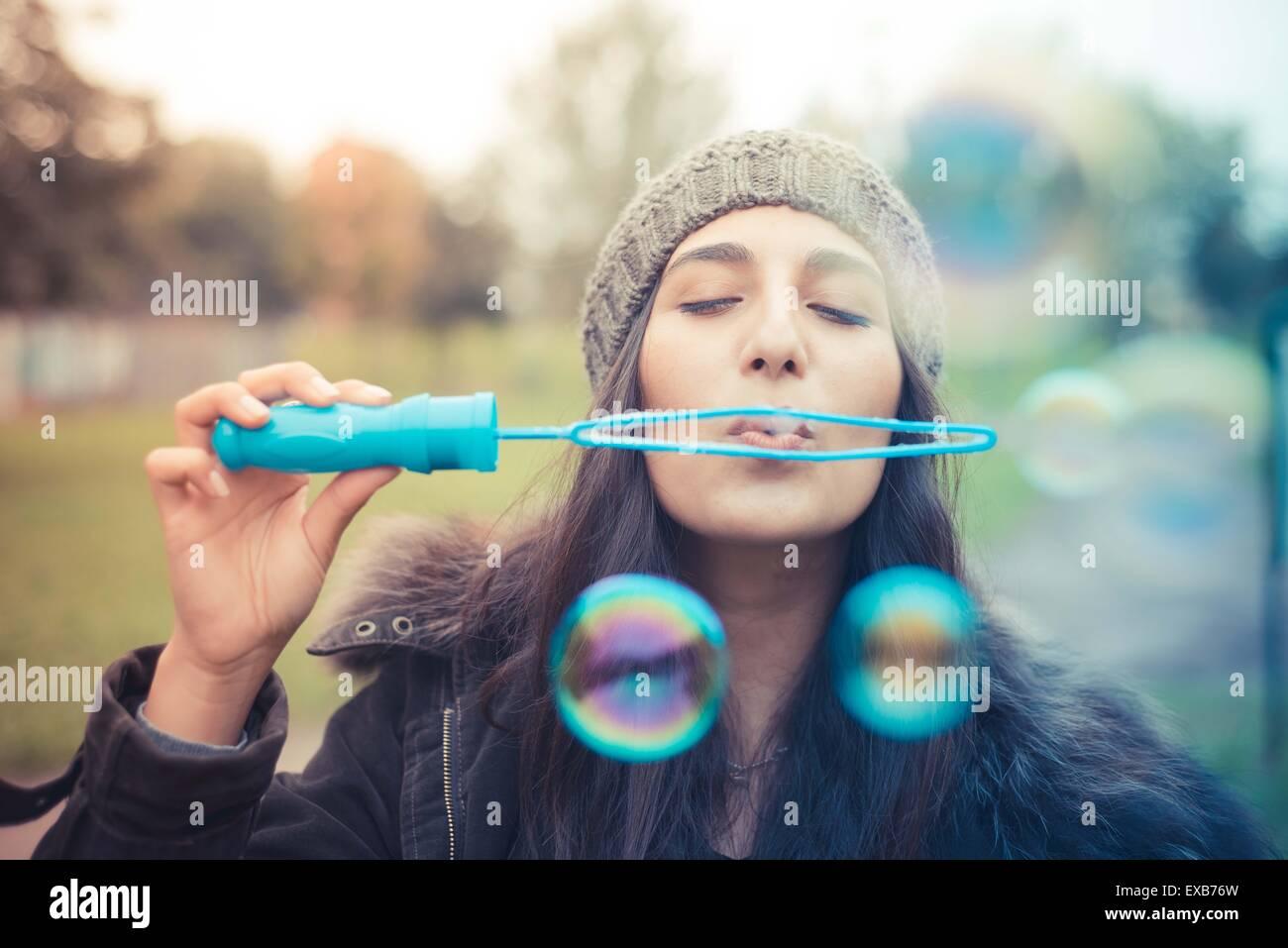 junge schöne Brünette Frau bläst Luftblasen Seife in der Stadt Stockbild