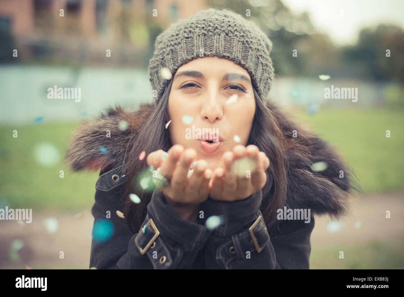 junge schöne Brünette Frau mit Konfetti-Karneval in der Stadt spielen Stockbild