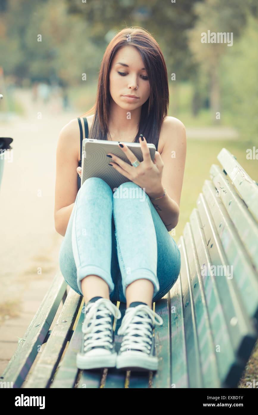 junge schöne Brünette glattes Haar Frau mit Tablet im freien Stockbild