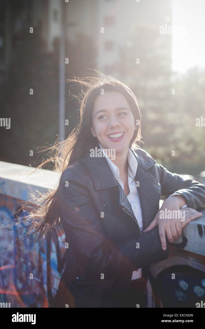 junge schöne lange Haare Frau in der Stadt bei Sonnenuntergang Hintergrundbeleuchtung Stockbild