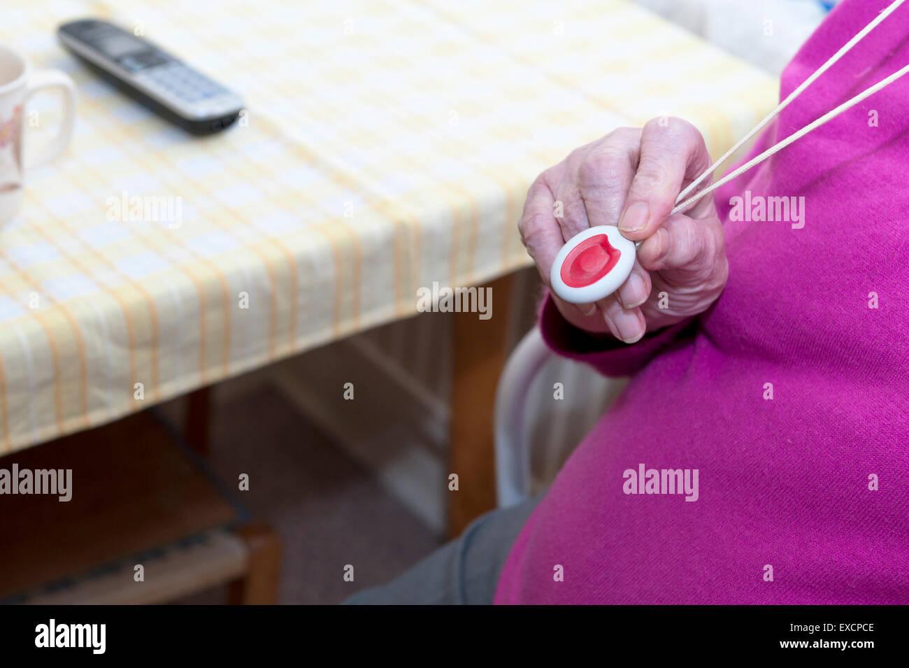 Die Hand von einer älteren Frau in ihre neunziger Jahre hält einen Lebensader Notfall Anhänger, die Stockbild