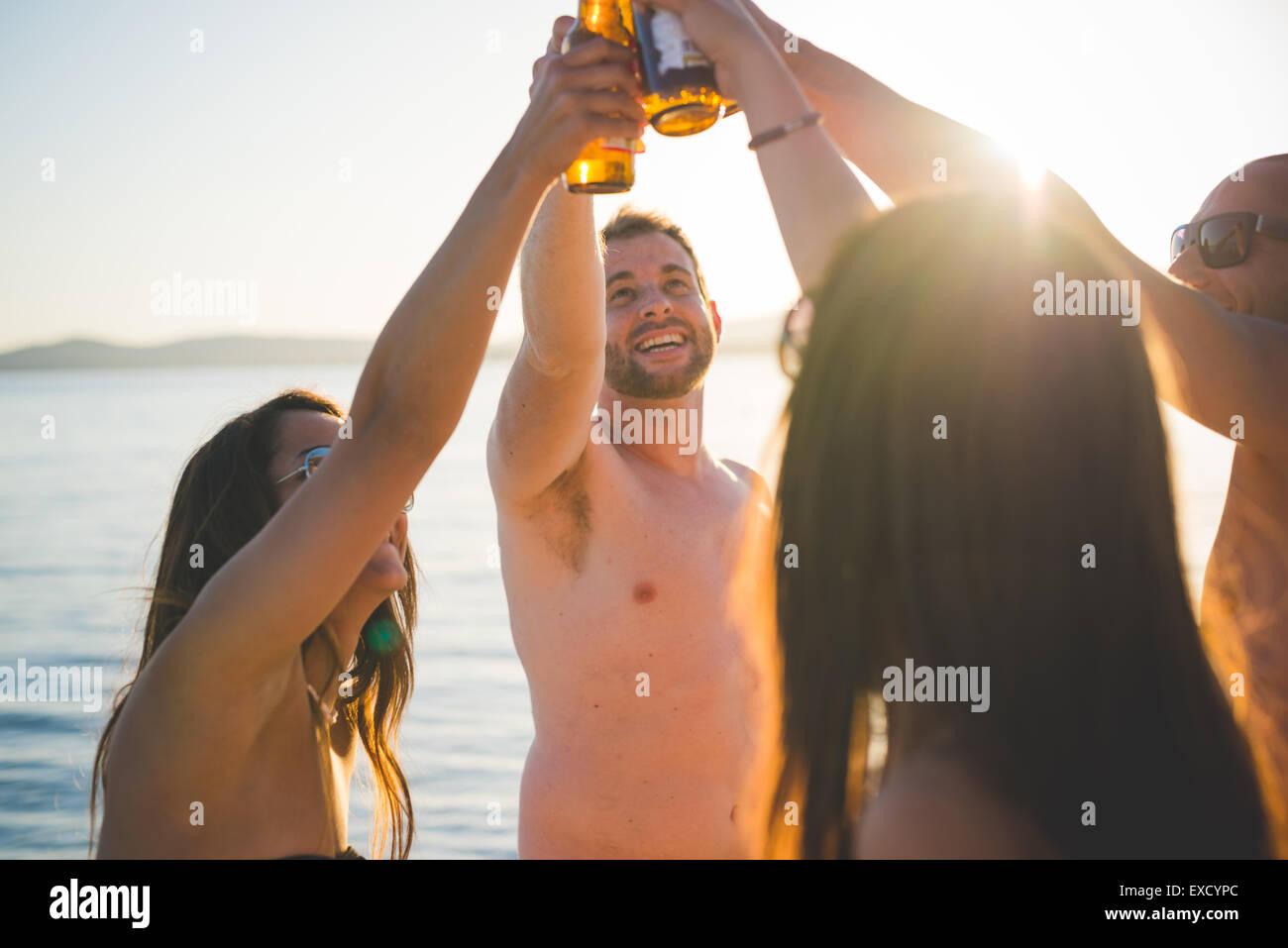 Gruppe von multiethnischen Jugendliche Frauen und Männer am Strand im Sommer Stockbild