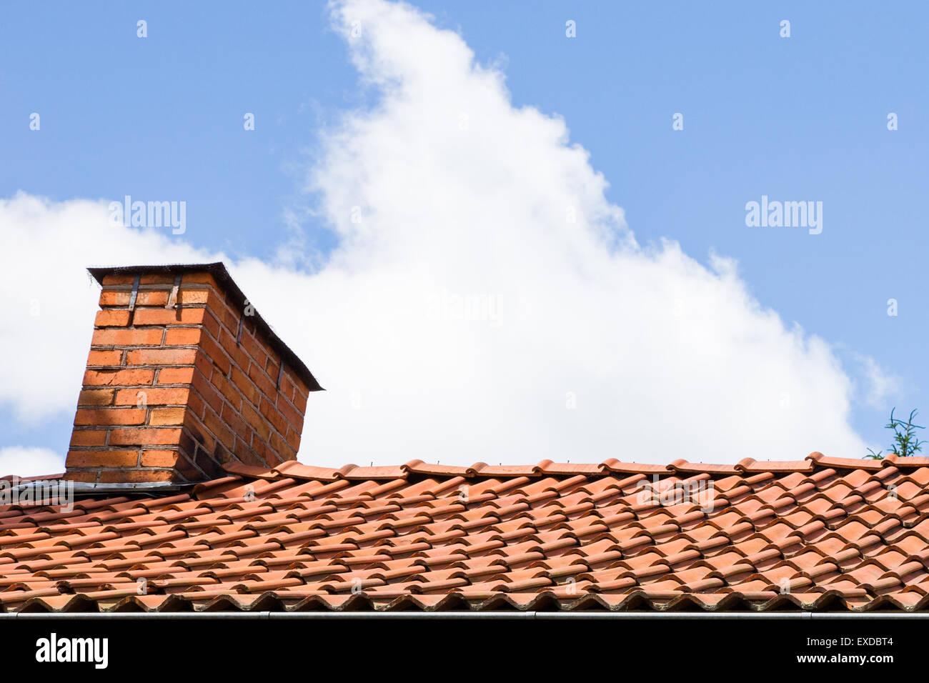 Ein roter Schornstein mit Fliesen und blauen Wolkenhimmel Stockfoto