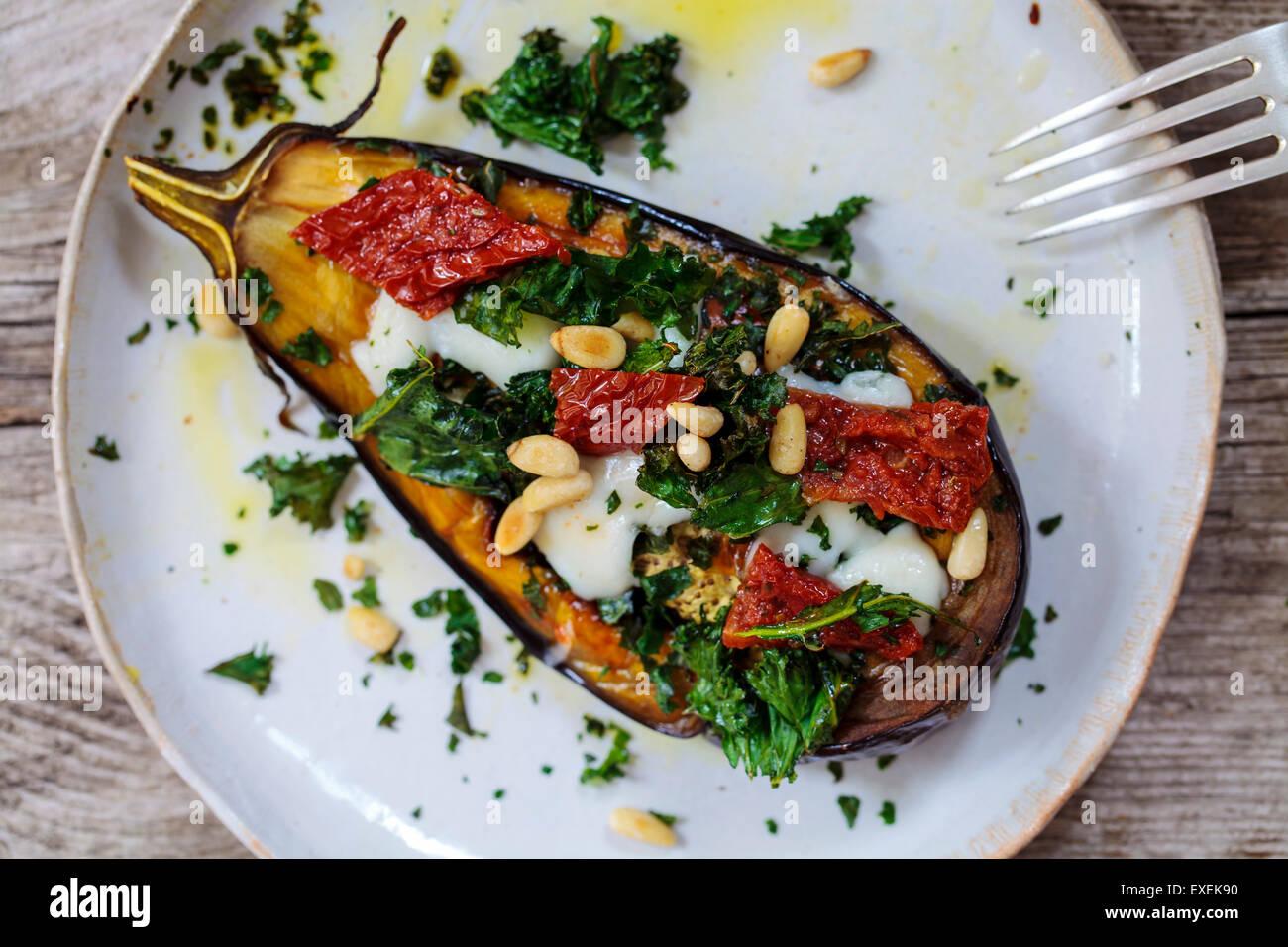 Gebratene Auberginen mit Ziegenkäse, knusprige Grünkohl, getrockneten Tomaten und Pinienkernen Stockbild