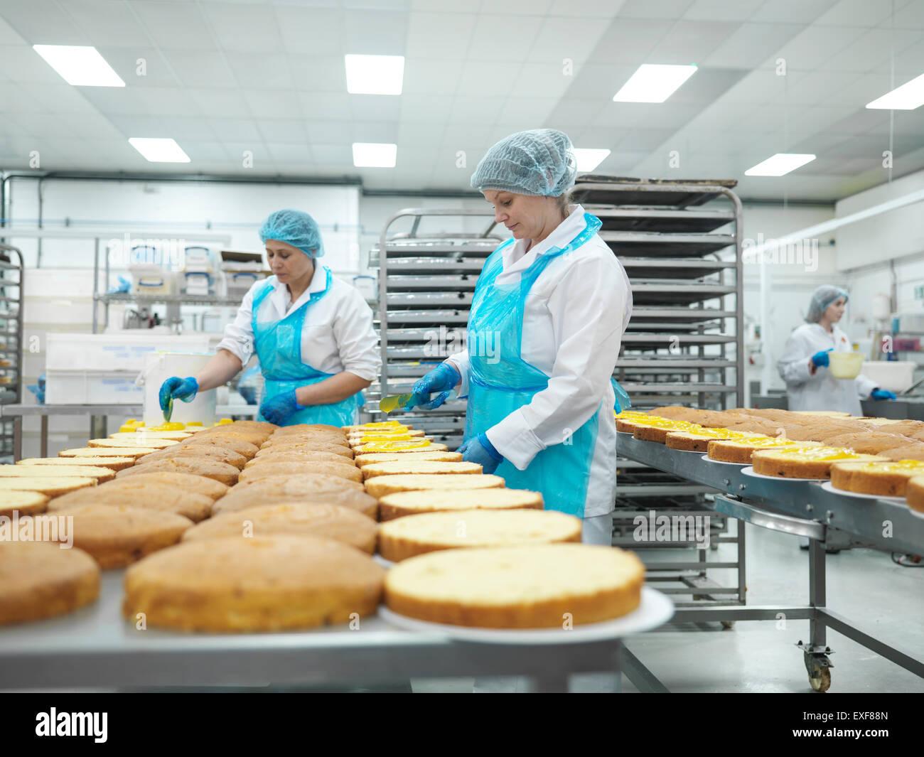 Arbeitnehmerinnen, die Verbreitung Füllung Kuchen Kuchenfabrik Stockbild