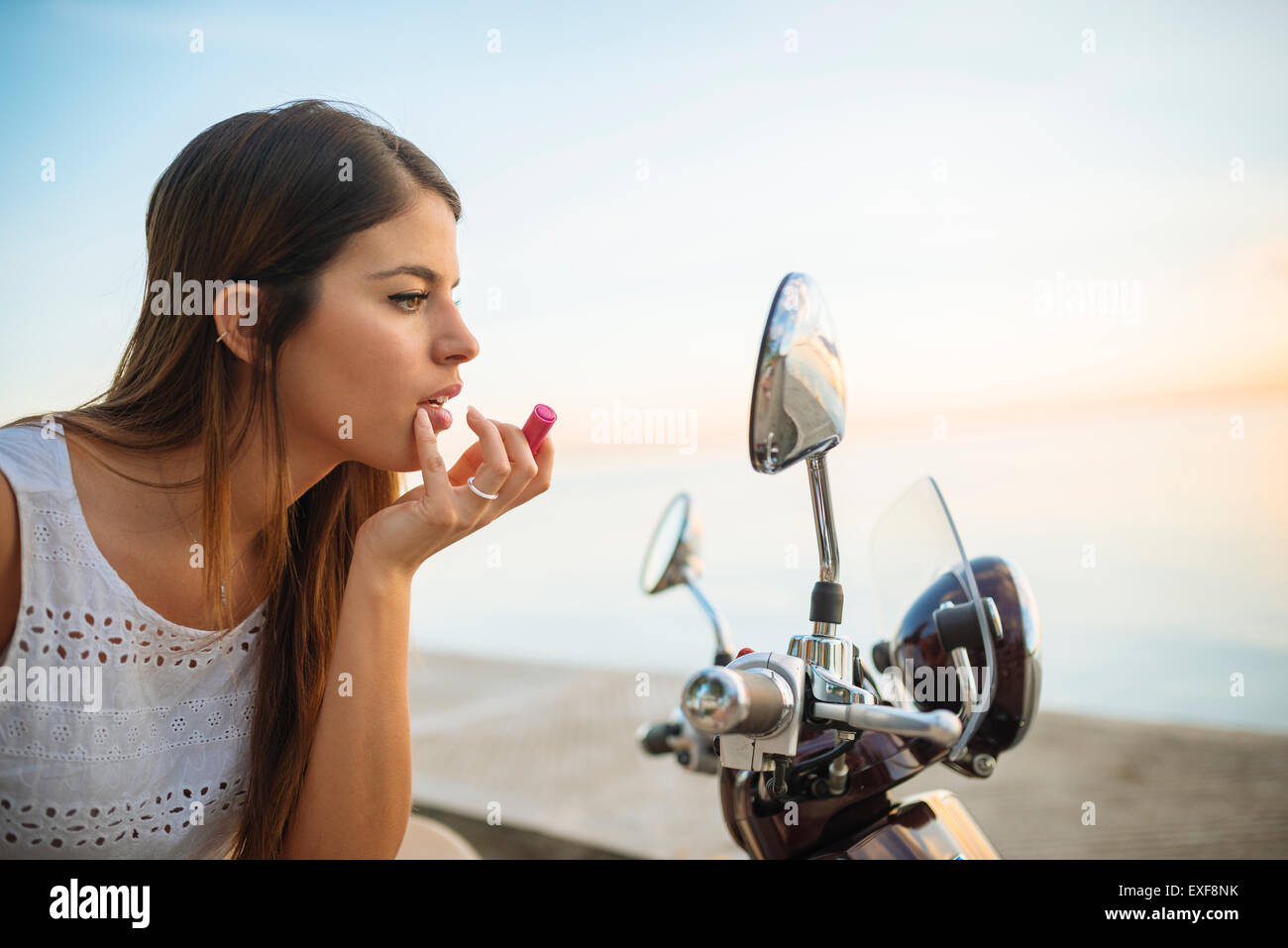 Junge Frau Auftragen von Lippenstift in Motorrad Spiegel, Manila, Philippinen Stockbild