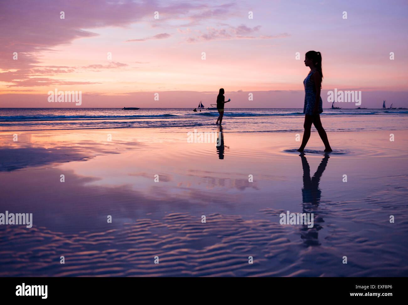 Silhouette junge Frau spazieren am Strand bei Sonnenuntergang, Insel Boracay, Visayas, Philippinen Stockbild