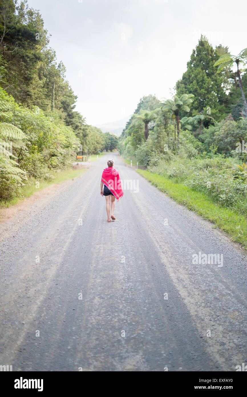 Frau zu Fuß entfernt, auf geraden Straße Stockbild