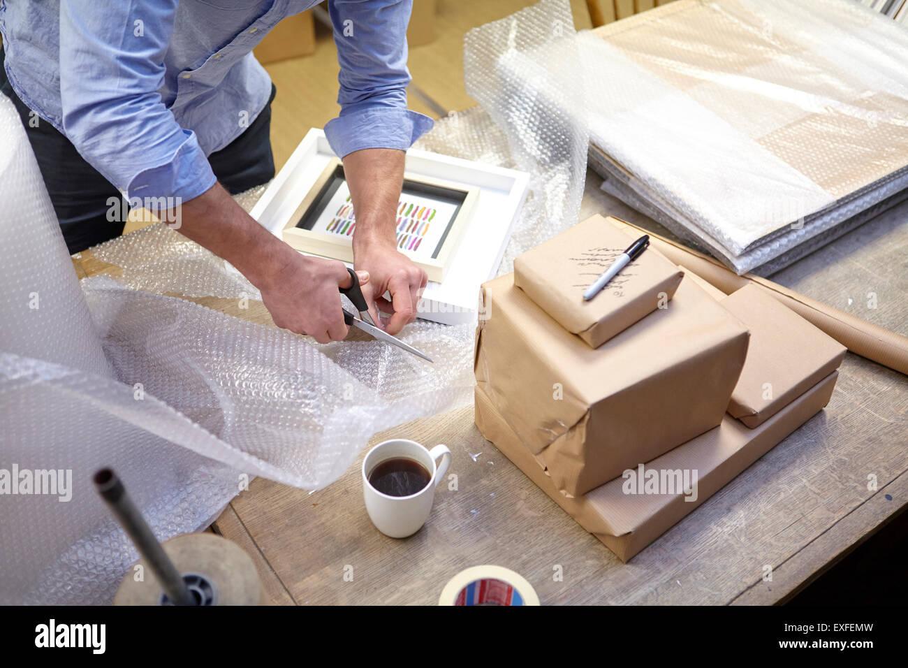 Mann schneiden Luftpolsterfolie auf Tabelle in Bild Einrahmer Werkstatt Stockbild