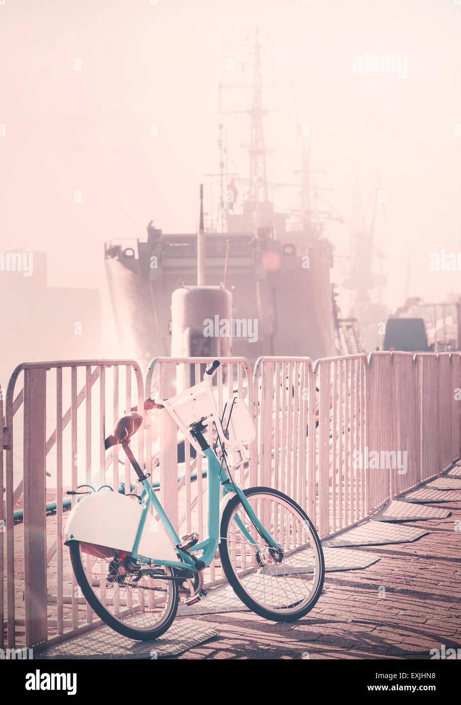 Vintage getönten Fahrrad geparkt Pier mit Schiff in der Ferne, Sonnenuntergang Lens-Flare-Effekt. Stockbild