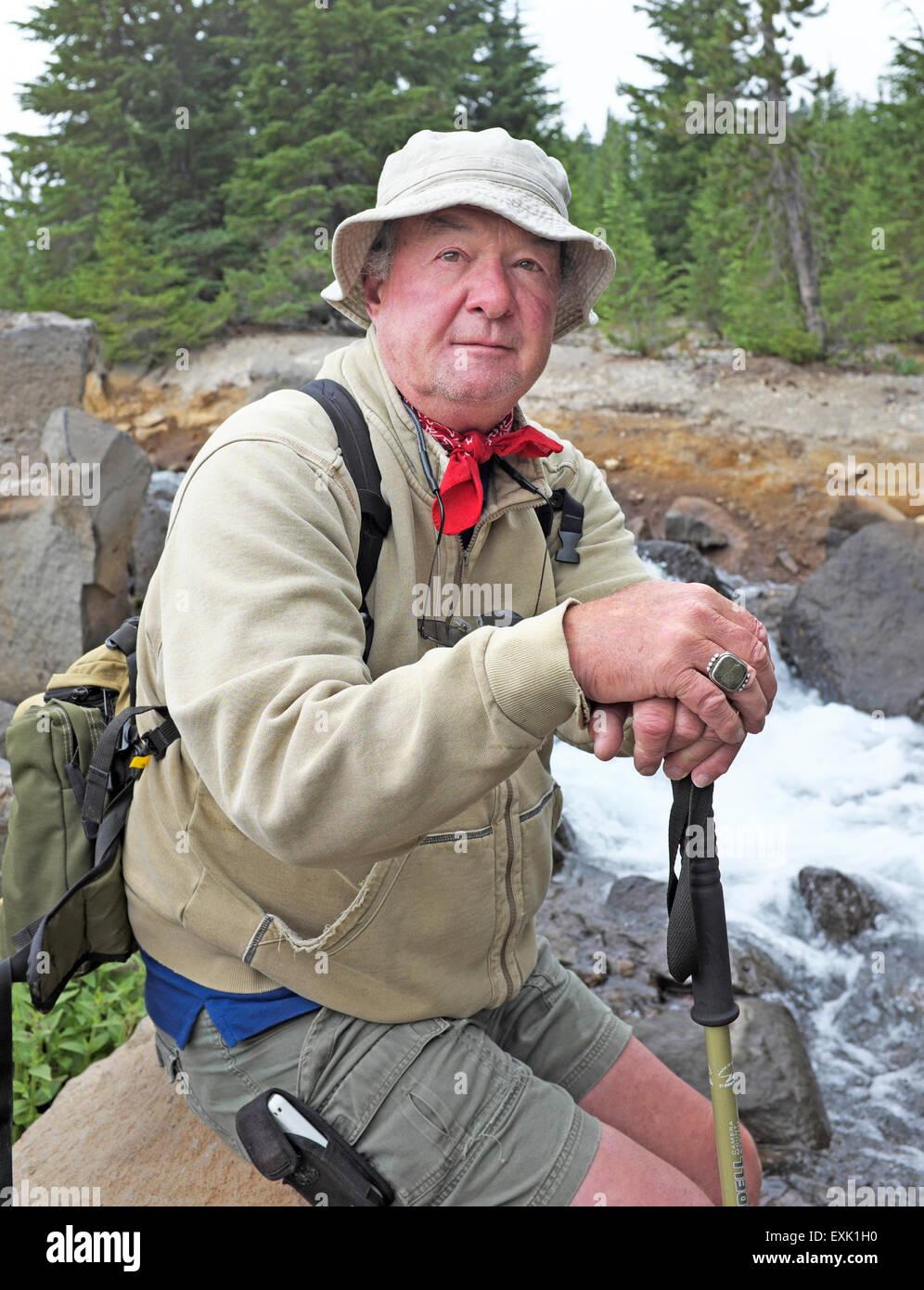 Ein älterer Wanderer sitzen neben einem Gebirgsbach in den Cascade Mountains of Oregon Stockbild