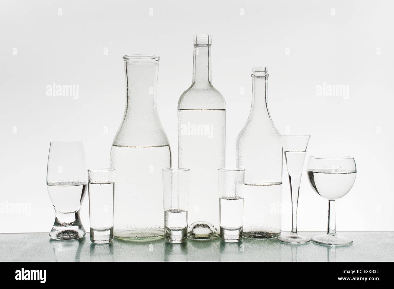 Glaswaren mit sauberem Wasser auf dem hellen Hintergrund Stockbild