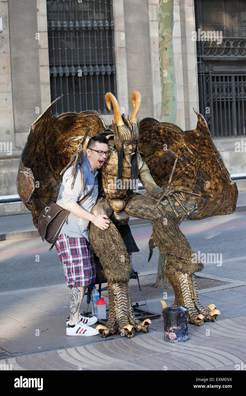 Straßenkünstler als live Teufel Statue, posiert mit einem Kerl auf der La Rambla in Barcelona, Katalonien, Stockbild